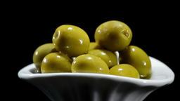 Green olives fruit gyrating on black background Footage
