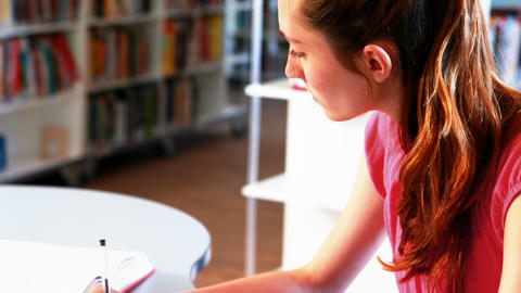 Attentive schoolgirl doing homework in library Live Action