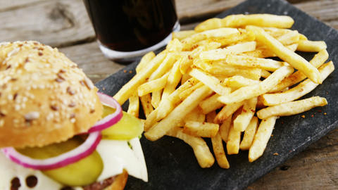 Hamburger, french fries and cold drink on slate board Live Action