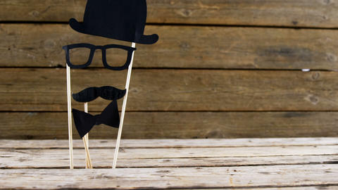 Bow tie, spectacles and fake mustache arranged on wooden plank Live Action