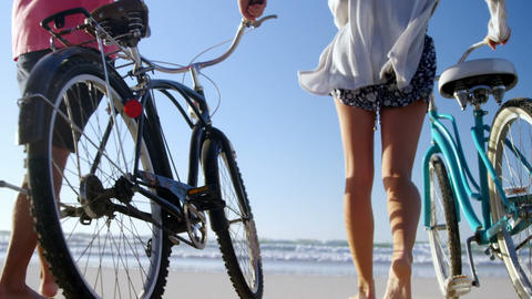 Couple walking with bicycles at beach on a sunny day Live Action