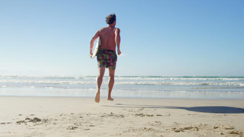 Man running with surfboard at beach on a sunny day Live Action