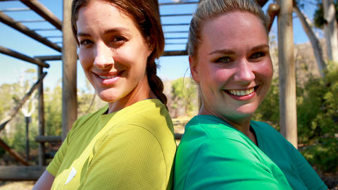 Portrait of confident friends standing back to back during obstacle course Live Action