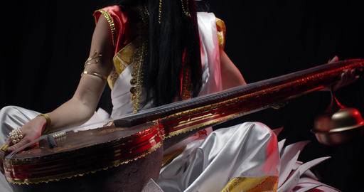 Close up of Saraswati in white dress with her music instrument veena, 4k Live Action