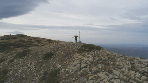 Male hiker standing on peak and victoriously raising arms rejoicing success Live Action