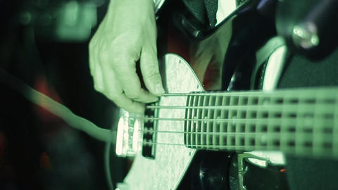 Close up of the hands of a rock guitarist and a bass guitar. Young professional Live Action