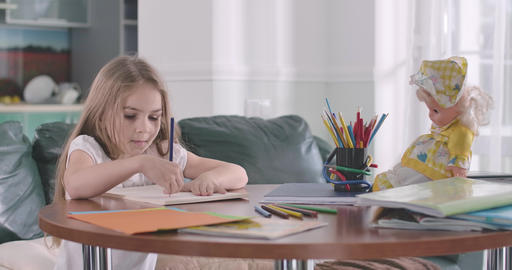 Little cute Caucasian girl doing math at home. Pretty child writing figures in Live-Action