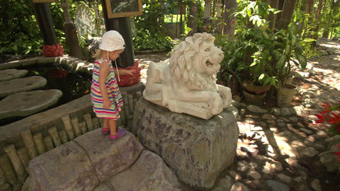 Small Girl Climbs on Lion Sculpture in Buddhist Temple Footage