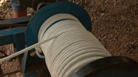 Man Winds Thick Rope to Coil of Zipline Machine in Park Footage