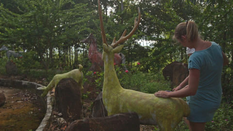 Small Girl Climbs on Deer Sculpture in Tropical Park Footage