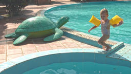 Little Girl Walks on Barrier Jumps into Pool by Toy Turtle Footage
