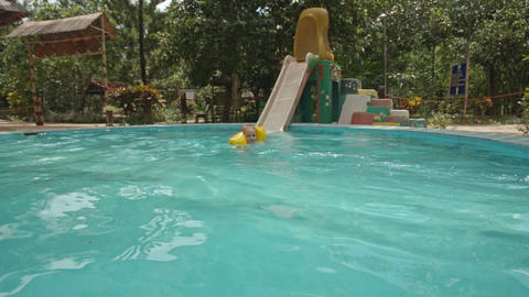 Little Girl Slides down from Water-slide into Pool Blue Water Footage