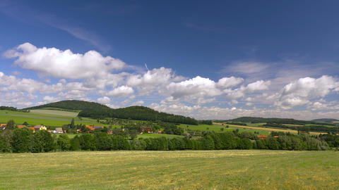 Timelapse clouds over green hills with village. Europe, Germany Footage