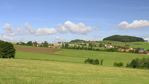 Clouds over green hills with village. Europe, Germany Footage