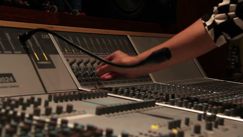 Recording studio music mixing desk console with engineer hand turning nob Footage