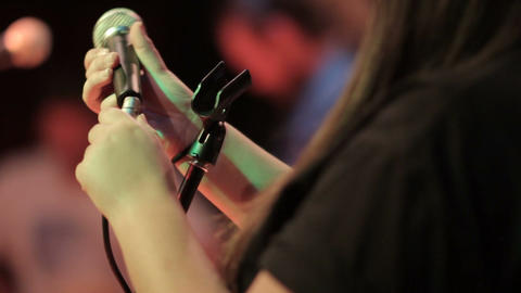 Hands plugging an XLR lead into a microphone in a music recording studio Footage