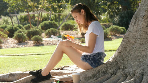 Girl Uni student studying on college campus under a tree with book and pen Footage