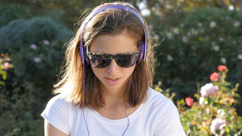 Attractive woman in 20s listening to music with headphones outdoors in park GIF