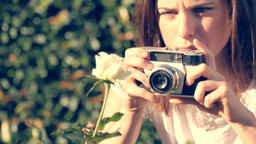 Girl with old retro camera practising photography by taking photo of a flower Footage