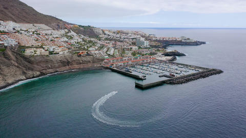 Aerial view of Los Gigantes, view of the marina and the city. Boat enters the Live Action