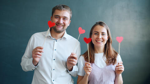 Playful couple holding hearts moving hands smiling feeling happy on Valentine's Live Action