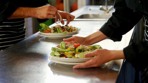 Chef offering a plate of salad at food station 4K 4k Live Action