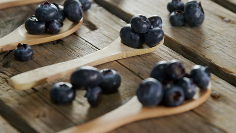 Spoons of blueberries arranged on wooden table 4k Live Action