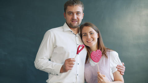 Portrait of beautiful couple holding heart shape lollipops on Valentine's day Live Action