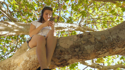 Young woman having fun on mobile smartphone technology sitting in autumn tree Footage