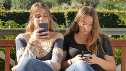Two bored teenage girl friends texting on social media Internet technology Footage