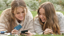 Young teenage friends online retail shopping purchasing item with credit card Footage