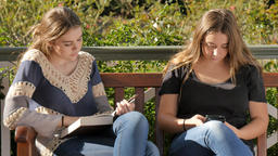 Young teenage girl students reading and using mobile smatphone to text and study Footage