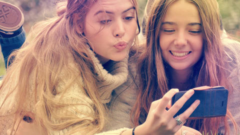 Two young woman pulling funny expression faces at mobile phone camera GIF 動畫