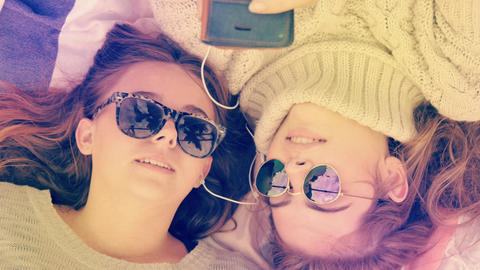 Stylish hip teenage girls with sunglasses listening to music sharing headphones GIF