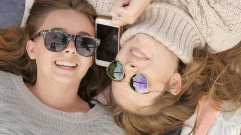 Teenage student girl friends listening to phone conversation laughing together Footage