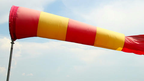 Red and yellow wind sock close-up shot, daytime cloudy weather Footage