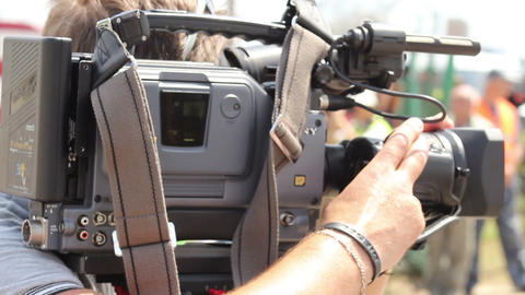 TV operator camera shoots report shots at day time, zooming Live Action