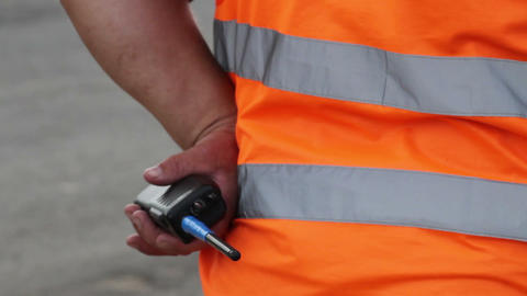 Clumsy security with walky-talky in orange uniform standing Live Action