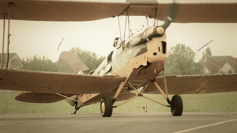Vintage biplane with spinning propeller steering on ground Footage