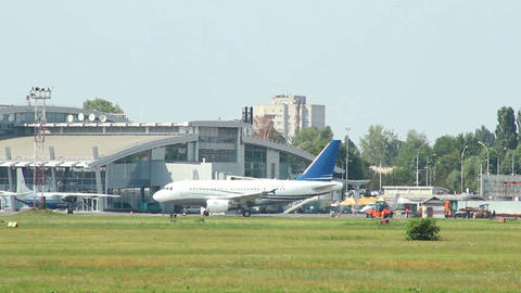 Airport activity at daytime, aircrafts steer by, planes parked Footage