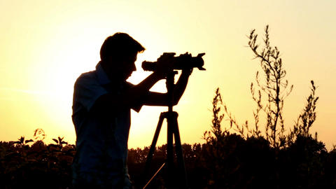 Young male shooting photo video at dusk, tripod camera shot Footage