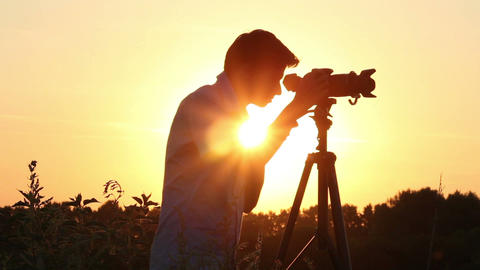 Young man shooting photo video in dusk dawn sun, camera Footage
