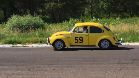 Bright yellow Volkswagen Beetle following Citroen 11B in racing of vintage cars Footage