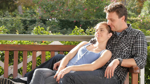 Young couple sitting in park cuddeling on park bench showing afection Live Action