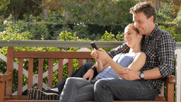 Millennial couple cuddling looking at smart phone device social media Footage