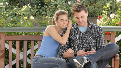 Sharing music headphone romantic young couple on park bench enjoying life Footage