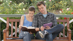Male and female uni students study for final exam with book tablet pc Footage
