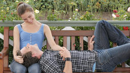 Caring young woman looks lovingly at her partner sitting romantically on bench Live Action