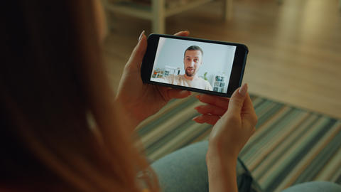 Slow motion of girl making video call with smartphone looking at gadget screen Live Action