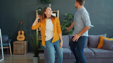 Husband and wife dancing together in apartment wearing casual clothing having Live Action